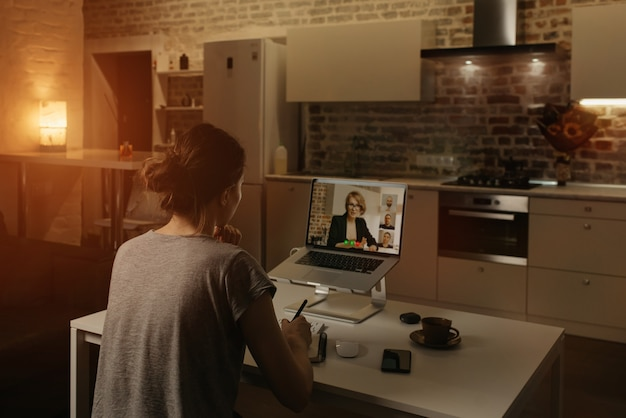 Vista posteriore di un'impiegata che lavora da remoto e prende appunti del discorso di un capo durante una videoconferenza su un laptop da casa.