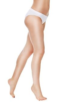 Vista posteriore di gambe femminili con mutandine bianche su uno spazio bianco