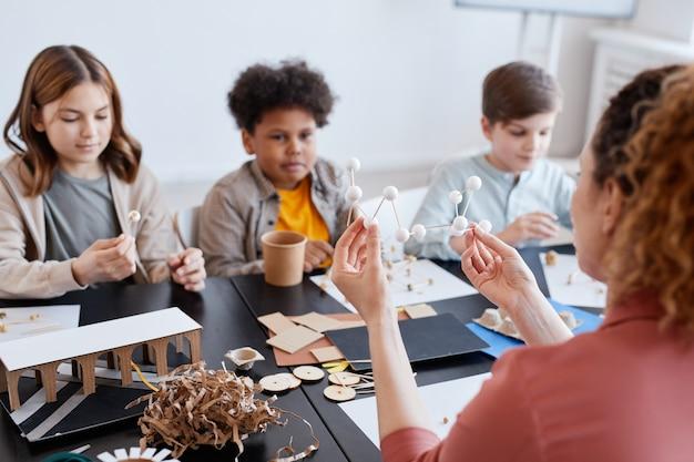Vista posteriore dell'insegnante femminile che dimostra modelli in legno a un gruppo di bambini durante le lezioni di arte e artigianato a scuola