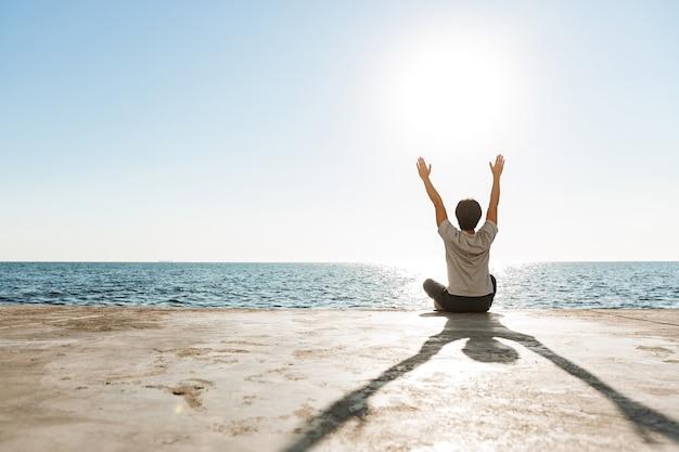 Vista posteriore di un uomo asiatico in forma che fa esercizi di yoga in spiaggia, meditando