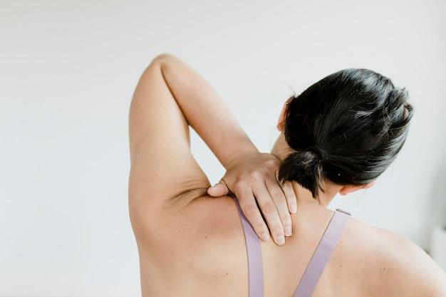 Vista posteriore della donna fitness che le raggiunge la schiena