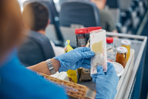 Vista posteriore dell'immagine focalizzata del tavolo con snack e bevande mentre hostess femminile serve pasti per il passeggero di prima classe