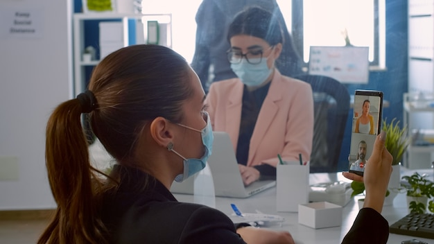 Vista posteriore di un uomo libero professionista con maschera facciale che parla in videochiamata con colleghi in remoto tramite telefono. donna d'affari che lavora nel nuovo normale ufficio aziendale durante la pandemia di covid19