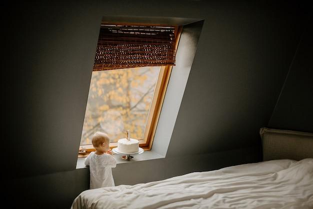 Vista posteriore dalla distanza di una bambina carina in piedi vicino a una finestra