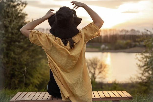 Vista posteriore di una ragazza con un cappello che si gode il tramonto seduta su una panchina nella foresta