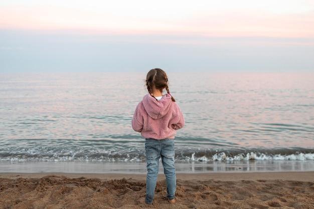 Ragazza di vista posteriore in riva al mare