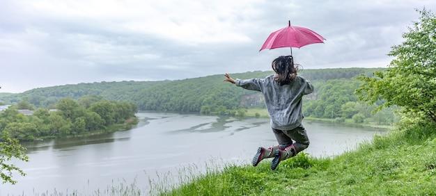 Vista posteriore di una ragazza sotto un ombrello che salta vicino a un lago in una zona montuosa in caso di pioggia.