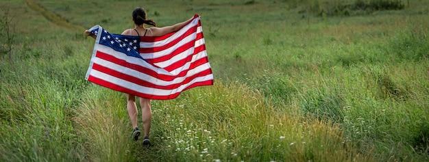 Vista posteriore di una ragazza con una bandiera americana che corre sull'erba nello spazio della copia del campo.