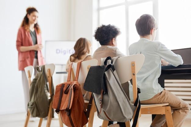 Vista posteriore di un gruppo di bambini seduti in fila e che usano i computer durante la lezione di informatica a scuola