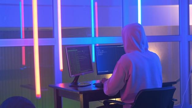 Vista posteriore del pirata informatico nel sistema di rete penetrante con cappuccio bianco nella stanza al neon
