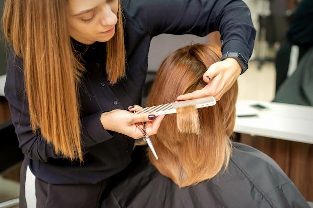 Il punto di vista posteriore del parrucchiere taglia i capelli rossi o marroni alla giovane donna nel salone di bellezza. taglio di capelli nel parrucchiere