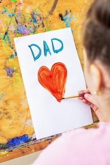 Vista posteriore della mano del bambino che disegna un cuore rosso con la parola papà biglietto di auguri su carta bianca su un cavalletto. concetto di famiglia e festa del papà.