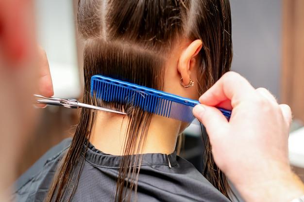 Vista posteriore delle mani del parrucchiere maschio taglia i capelli lunghi della giovane donna nel parrucchiere