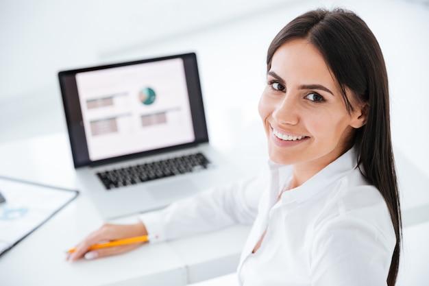 Punto di vista posteriore della donna felice di affari che si siede dalla tavola con il computer portatile in ufficio. immagine ravvicinata
