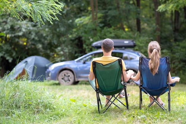 Vista posteriore di una coppia felice seduta su sedie in campeggio rilassante insieme.