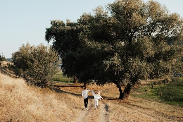 Vista posteriore della coppia felice trascorre del tempo insieme alla natura. in estate camminano per la strada nei boschi.