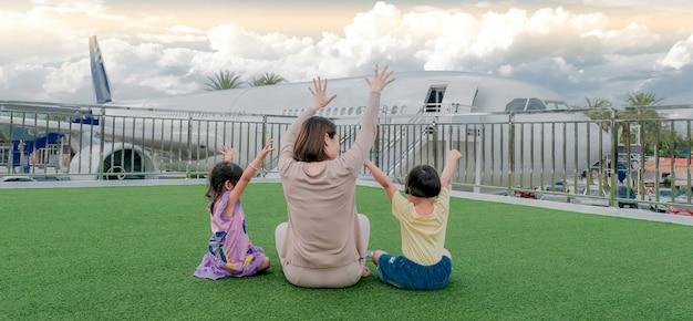 La vista posteriore della donna madre di famiglia felice e dei bambini piccoli, alzando le braccia divertendosi a salutare l'aereo.