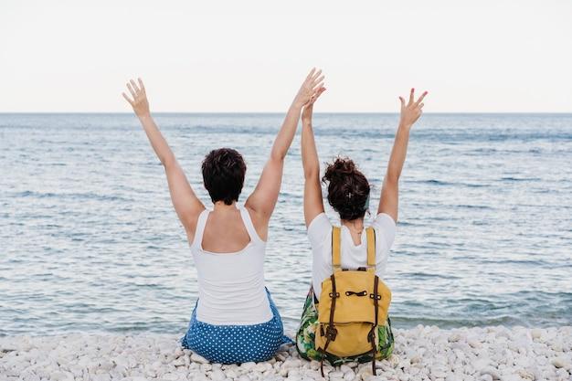 Vista posteriore di una coppia lesbica felice seduta in spiaggia con le braccia alzate durante il tramonto. l'amore è amore e concetto lgtbi