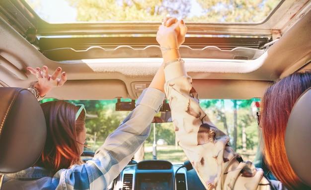 Vista posteriore di giovani amiche felici che si tengono per mano e alzano le braccia all'interno dell'auto in un'avventura di viaggio su strada. amicizia femminile e concetto di tempo libero.