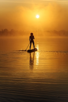 Vista posteriore di un uomo sano e attivo in silhouette canottaggio con paddle board sul lago.