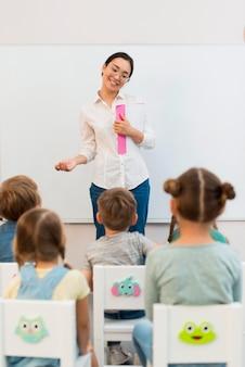 Vista posteriore dei bambini che prestano attenzione al loro insegnante