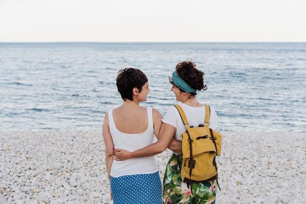 Vista posteriore della coppia lesbica che si abbraccia in spiaggia durante il tramonto. l'amore è amore e concetto lgtbi