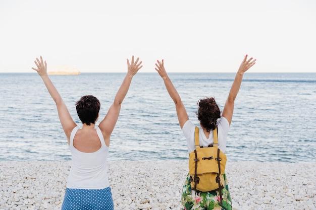 Vista posteriore della coppia lesbica con le braccia alzate di felicità in spiaggia durante il tramonto. l'amore è amore e concetto lgtbi