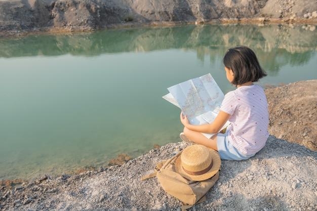 Vista posteriore piccola ragazza asiatica lato posteriore della ragazza viaggiatrice che cerca la giusta direzione sulla mappa