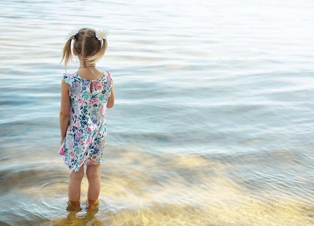 Vista posteriore della bambina in piedi in acqua in spiaggia