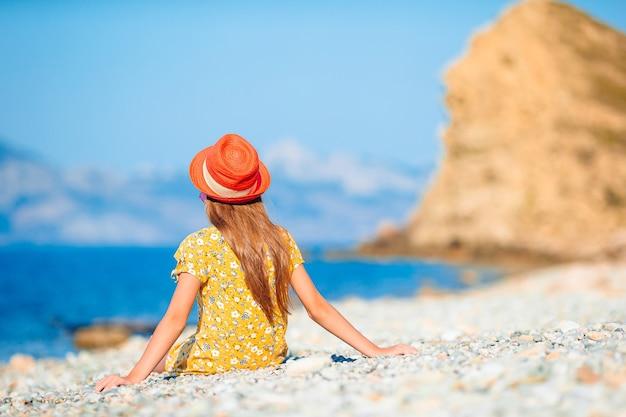 Vista posteriore della bambina in abito bianco al cappello sulla spiaggia