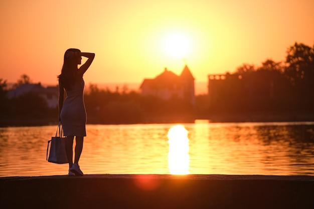 Vista posteriore della donna sola in piedi sul lato del lago in una calda serata. concetto di solitudine e relax.