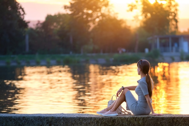 Punto di vista posteriore della giovane donna sola che si siede da solo sulla riva del lago che gode della serata calda. benessere e relax nel concetto di natura.