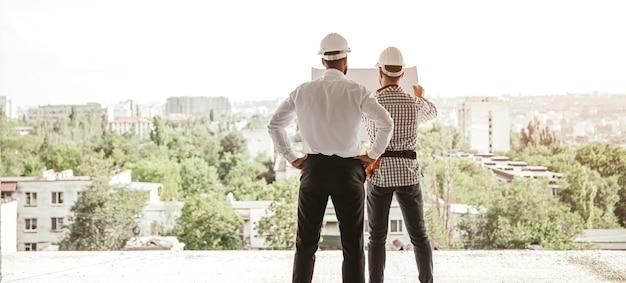 Vista posteriore di architetti maschi in elmetti protettivi che esaminano il progetto e discutono del progetto di costruzione mentre stanno contro il paesaggio urbano con edifici moderni