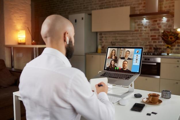 Vista posteriore di un impiegato maschio in auricolari che sta prendendo appunti su una videoconferenza aziendale su un laptop.