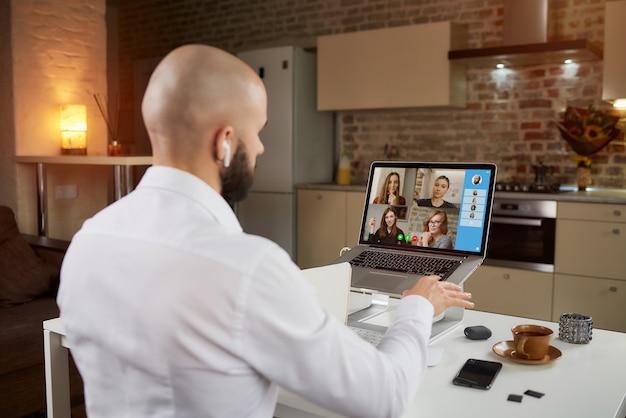 Vista posteriore di un impiegato maschio in auricolari che sta spiegando e gesticolando in una videoconferenza aziendale su un laptop.
