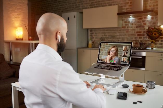 Vista posteriore di un impiegato maschio in auricolari che sta ascoltando il discorso di un capo in una videoconferenza aziendale su un laptop.