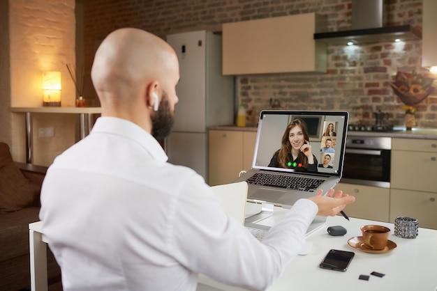 Vista posteriore di un dipendente di sesso maschile in auricolari che sta lavorando gesticolando in remoto durante una videoconferenza di lavoro su un laptop a casa.