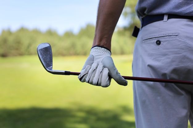 Punto di vista posteriore di un giocatore di golf maschio al corso verde.