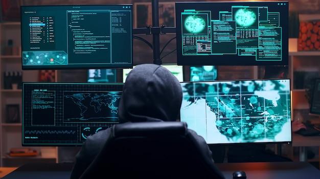 Vista posteriore di un hacker maschio che indossa una felpa con cappuccio che infetta il server del governo con un virus pericoloso.