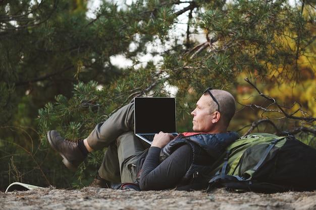 Vista posteriore, escursionista maschio sdraiato sulla schiena appoggiato allo zaino, con computer portatile, digitazione, blog, navigazione nella foresta