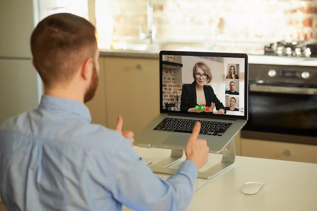 Punto di vista posteriore del maschio che ascolta i rapporti dei suoi colleghi durante una videoconferenza.