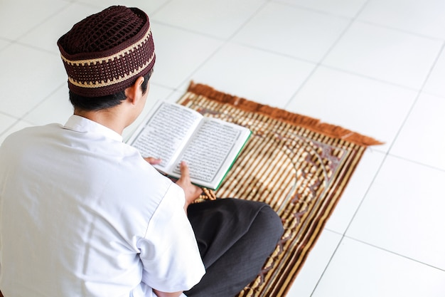 Vista posteriore dell'uomo musulmano che tiene e legge il libro sacro alquran sul tappetino da preghiera