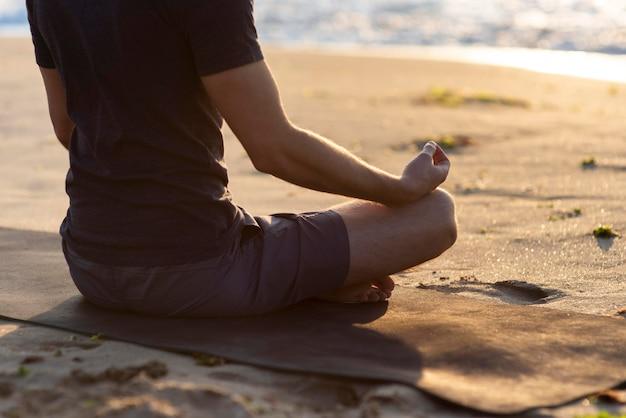 Uomo di vista posteriore che si distende sulla spiaggia con lo spazio della copia