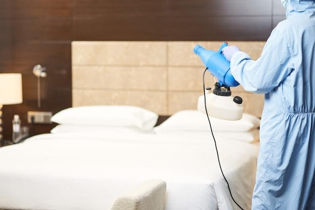 Vista posteriore dell'uomo in tuta protettiva contro il virus che disinfetta la stanza del virus corona con lo spruzzatore. coronavirus e concetto di quarantena. copia spazio