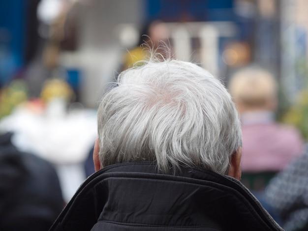 Vista posteriore dell'uomo con una testa di capelli grigi all'aria aperta.