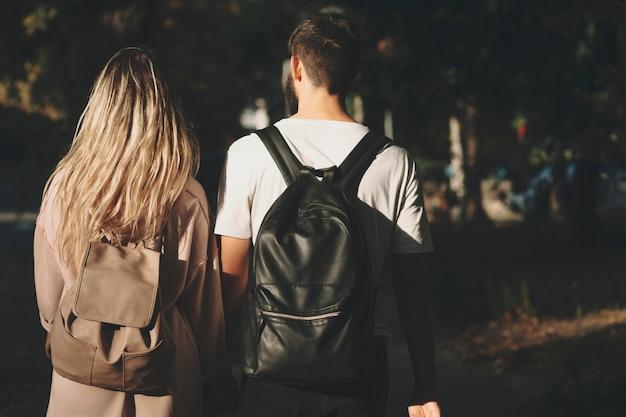 Vista posteriore di un uomo e di una donna che indossa zaini e in piedi insieme nel parco soleggiato