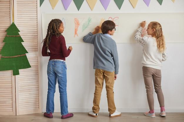 Vista posteriore al gruppo multietnico di bambini che disegnano sui muri mentre godono del corso d'arte a scuola, copia dello spazio