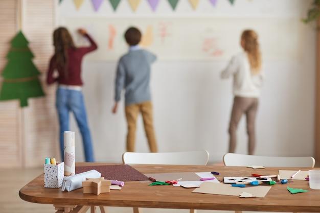 Vista posteriore al gruppo multietnico di bambini che disegnano sui muri mentre si godono le lezioni di arte a scuola con focus sulla tavola di lavorazione in primo piano, spazio di copia