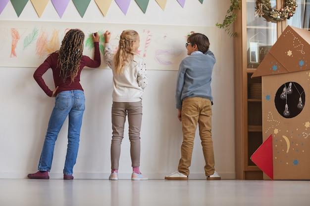 Vista posteriore al gruppo multietnico di bambini che disegnano sui muri mentre si godono le lezioni d'arte a scuola, copia dello spazio