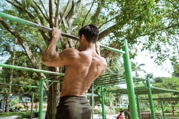 Vista posteriore di un uomo muscoloso senza vestiti facendo esercizi di pull-up utilizzando la barra di ferro nel parco